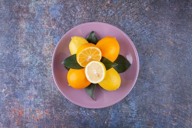 Hele en gesneden citroenvruchten die op een steen worden geplaatst.