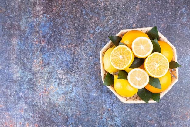 Hele en gesneden citroenvruchten die op een steenachtergrond worden geplaatst.