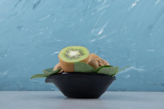 Hele en gesneden kiwi's in zwarte kom