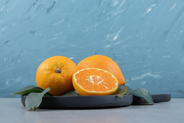 Hele en gesneden mandarijnen op zwarte snijplank.