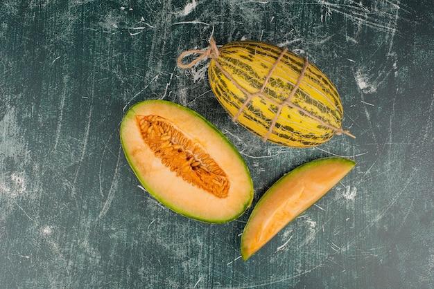 Hele en gesneden meloenen op marmeren oppervlak.