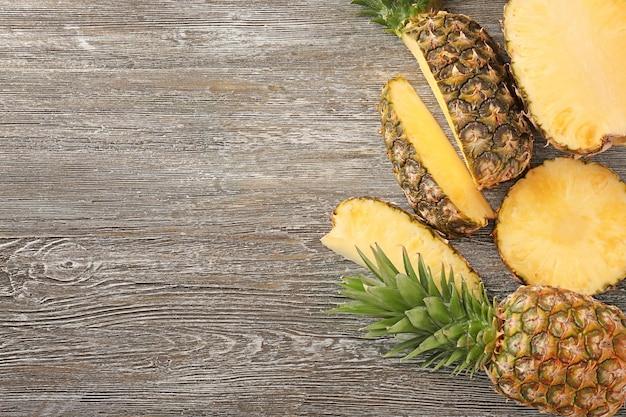 Hele en gesneden rijpe ananas op houten achtergrond