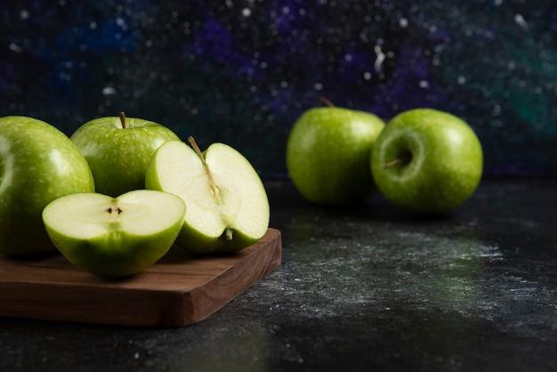Hele en gesneden rijpe groene appels op een houten bord.