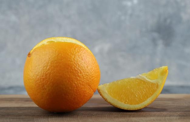 Hele en gesneden sinaasappel op marmeren tafel.