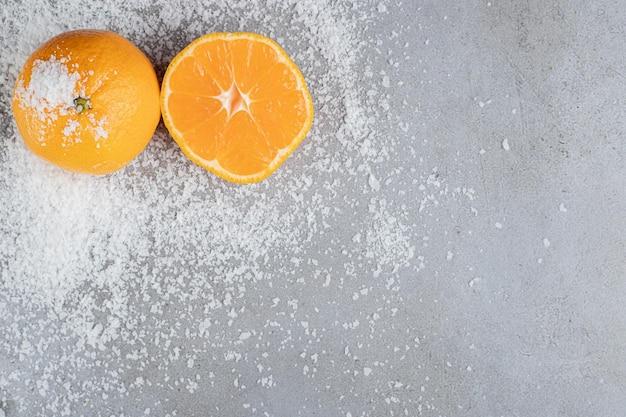 Hele en gesneden sinaasappelen zitten in verspreid kokospoeder op marmeren oppervlak