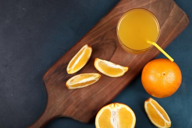 Hele en gesneden sinaasappels met een glas sap. bovenaanzicht