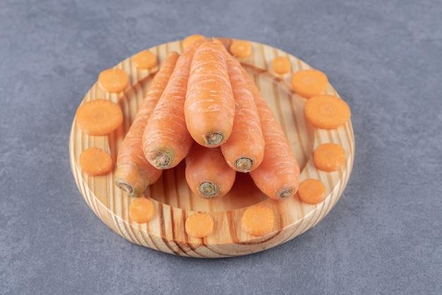 Hele en gesneden wortelen in de houten plaat, op het marmeren oppervlak.