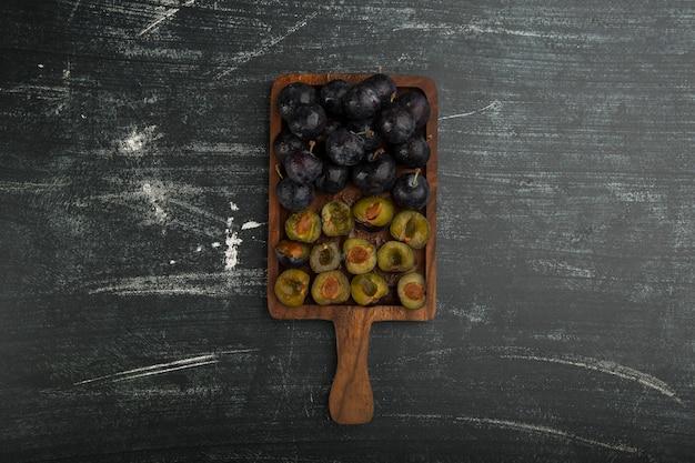 Hele en gesneden zwarte pruimen op een houten bord in het midden