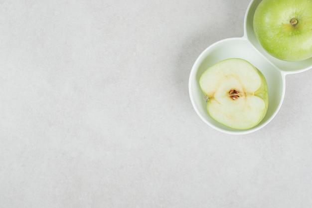 Hele en halve gesneden groene appels in witte kommen