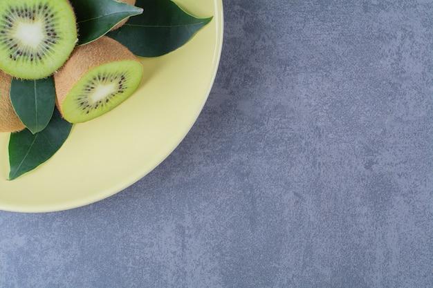 Hele en halve kiwi's op plaat op marmeren tafel.