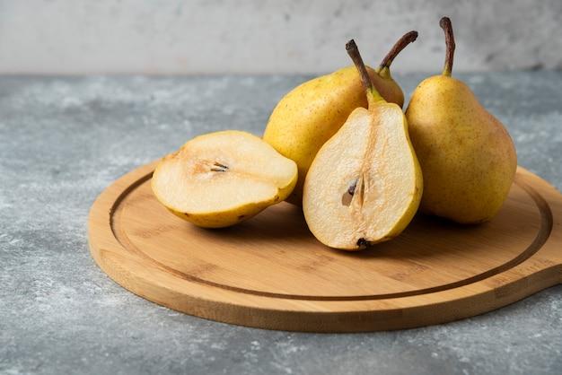 Hele en halve peren op een houten bord.