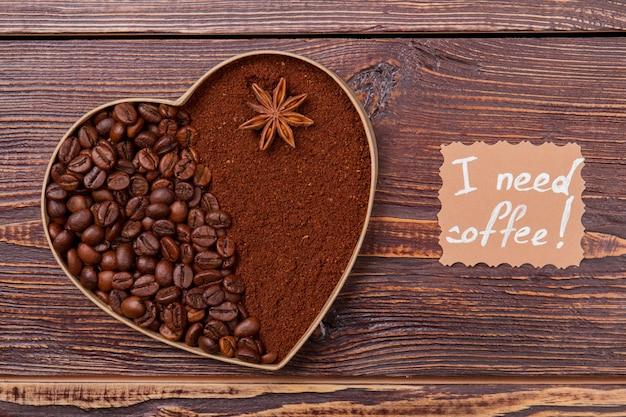 Hele en instant koffie gearrangeerd in een vorm van hart. een met een deel gevuld met koffiebonen en een ander met oploskoffie. ik heb koffie nodig.