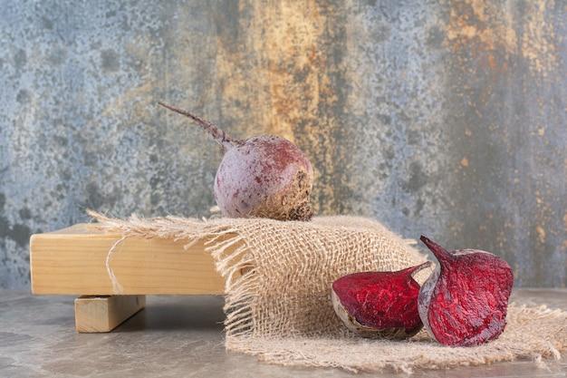 Hele en twee helften van rode bieten op een houten bord