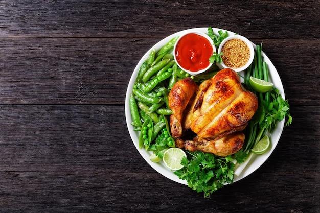 Hele gebraden kip geserveerd met gebakken peulen van doperwten, verse groene ui, peterselie, limoen, tomatensaus en volkoren mosterd op een witte plaat op een donkere houten tafel, plat leggen, vrije ruimte