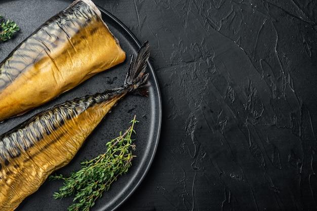 Hele gerookte vismakreel, op zwarte tafel, bovenaanzicht plat lag met kopie ruimte