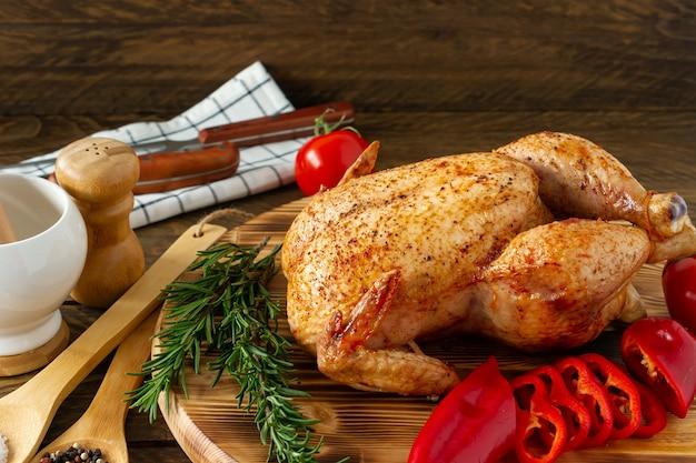 Hele geroosterde kip op een houten bord geserveerd met verse groenten en kruiden.