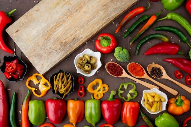 Hele, gesneden en gezouten paprika's met kruiden en broccoli en snijplank op kastanjebruine tafel