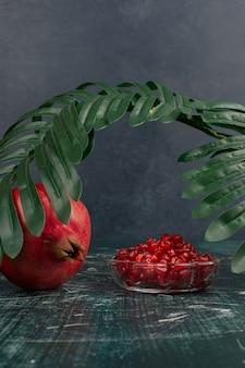 Hele granaatappel en zaden op marmeren tafel