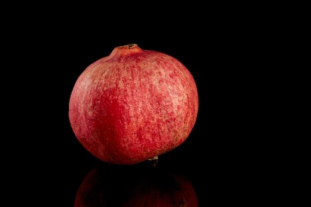 Hele granaatappelfruit op zwarte achtergrond