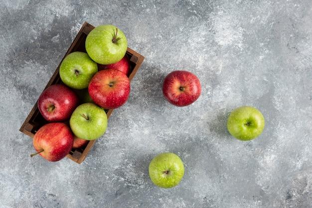 Hele groene appels en kaneelstokjes op marmeren tafel.