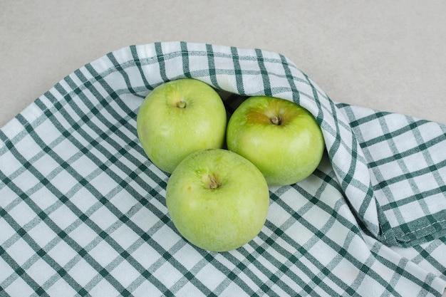 Hele groene appels op gestreept tafelkleed