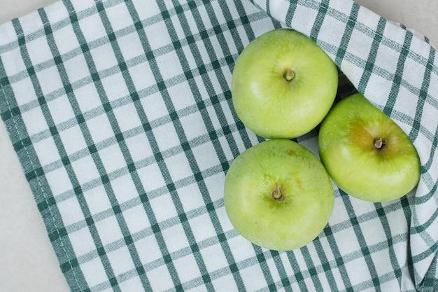 Hele groene appels op gestreept tafelkleed Gratis Foto