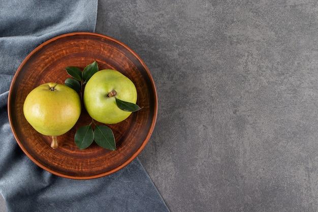 Hele groene peren op een stenen tafel.