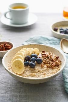 Hele havermout, grote kom pap met banaan, bessen, noten voor het ontbijt. zijaanzicht, verticaal