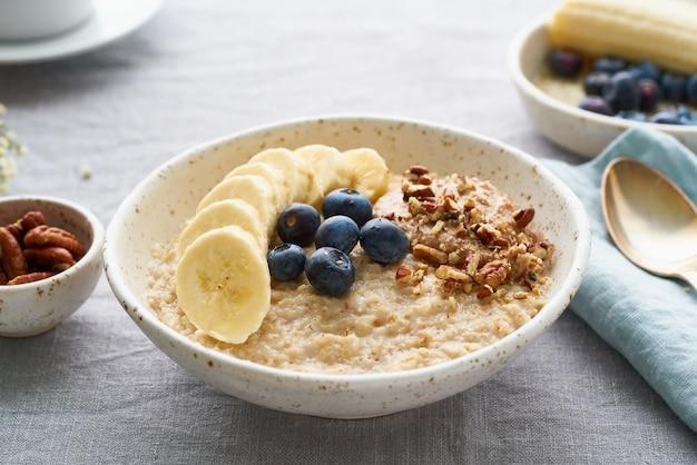 Hele havermout, grote kom pap met banaan, bosbessen, noten als ontbijt,