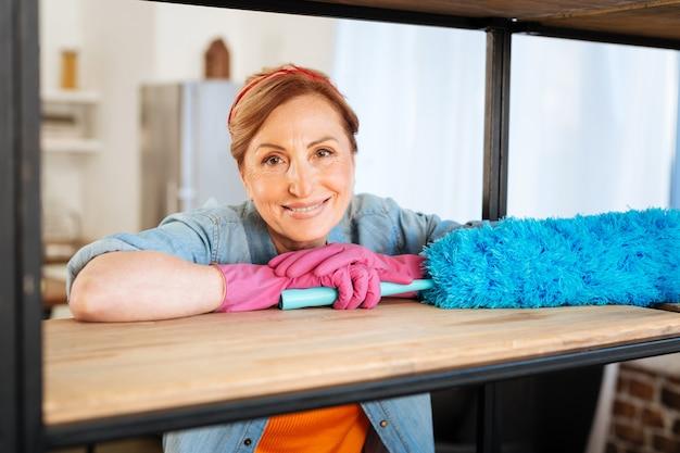 Hele huis schoonmaken. aangename stralende volwassen vrouw leunend op houten plank terwijl ze blauwe pluim draagt