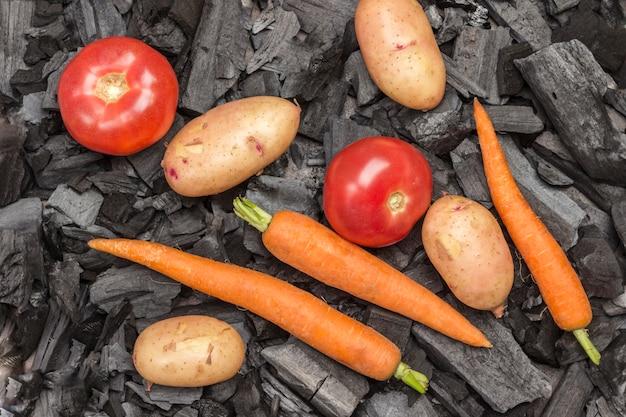 Hele jonge aardappelen, tomaten, wortelen, dille en koriander op houtskool. gegrild eten. biologische gezonde voeding. plat leggen