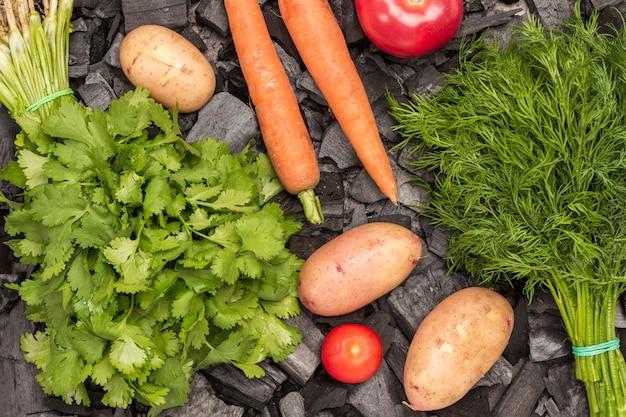 Hele jonge aardappelen, tomaten, wortelen, dille en koriander op houtskool. gegrild eten.