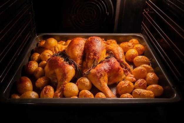 Hele kip en aardappelen roosteren in de oven.