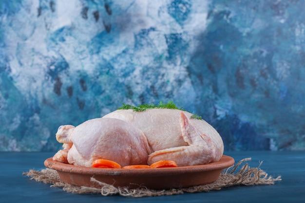 Hele kip en gesneden wortelen op een bord op een jute servet op het blauwe oppervlak