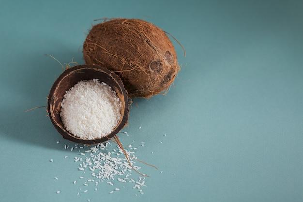 Hele kokosnoot met kokosnotenvlokken op een blauw