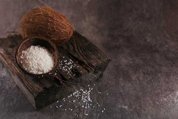 Hele kokosnoot met kokosvlokken op een donkere achtergrond