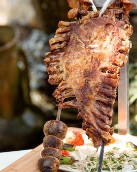 Hele lamsribben kebab en gegrilde aardappelen op stalen spiesjes