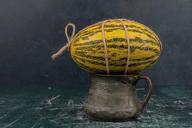 Hele meloen met touw bovenop vaas op marmeren tafel