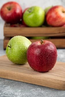 Hele natte groene en rode appels op houten snijplank.
