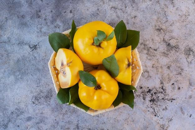 Hele of half gesneden appelkweeën in een mand boven rustiek.