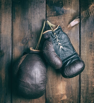 Hele oude shabby lederen bokshandschoenen opknoping op een spijker