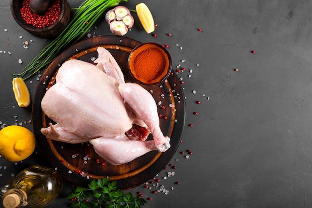 Hele rauwe kip op de houten snijplank en kruiden om het bovenaanzicht te koken.