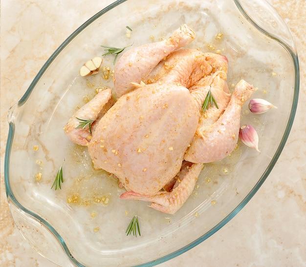Hele rauwe kip op marmeren tafel