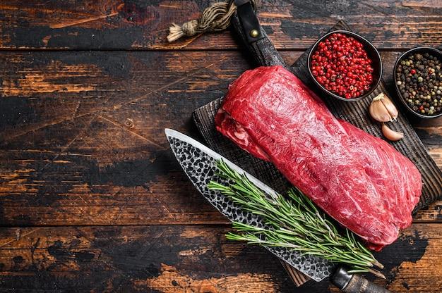 Hele rauwe ossenhaas kalfsvlees voor steaks filet mignon op een houten snijplank met slagersmes