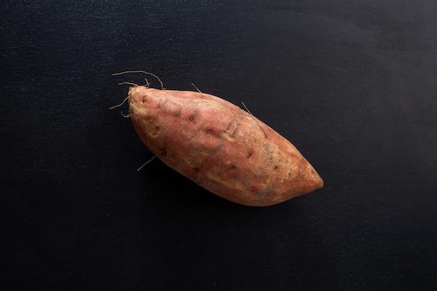 Hele rauwe zoete aardappel op donkere achtergrond. mockup. detailopname