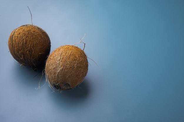 Hele rijpe verse kokosnoot set, op blauwe getextureerde zomer achtergrond, met kopie ruimte voor tekst
