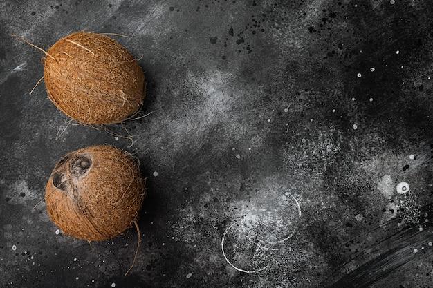 Hele rijpe verse kokosnoot set, op zwarte donkere stenen tafel achtergrond, bovenaanzicht plat lag, met kopieerruimte voor tekst
