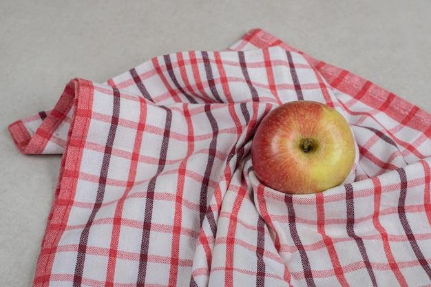Hele rode appel op gestreept tafelkleed