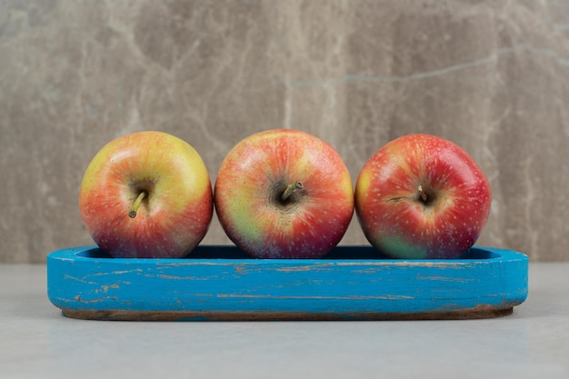 Hele rode appels op blauw bord.