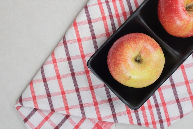 Hele rode appels op zwarte plaat met tafellaken